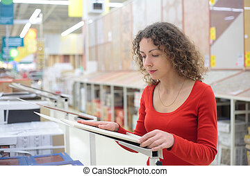 young woman in shop chooses ceramic tile