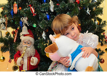 Little girl with soft toy under New Year`s tree
