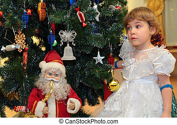 Little girl  under New Year`s tree