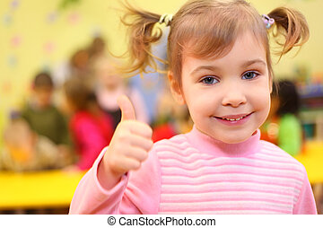 Little smiling girl in kindergarten shows sign ok