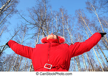 Young woman with rised hands looks in sky