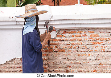 Builders are using a chisel and hammer to punch a brick...