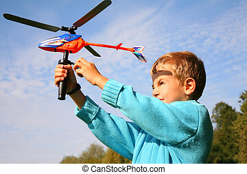 boy starts toy helicopter