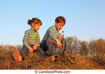 Little girl and boy with bottle and stick in striped t-shirts sit on dry grass