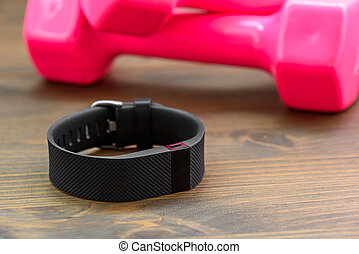 Sports tracker and pink dumb-bell - wearable device, wirst...