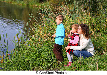 Mother with children sits on bank of pond