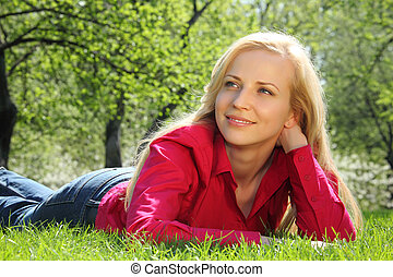 beautiful blonde lies on grass in park in spring