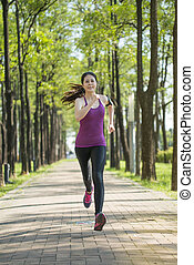 Asian young woman jogging in the forest, outdoors