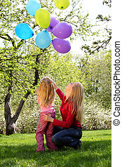 Mother with daughter with sheaf of balloons in  garden in spring