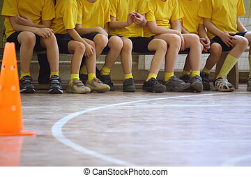 Children\'s feet in sports hall, sit on bench