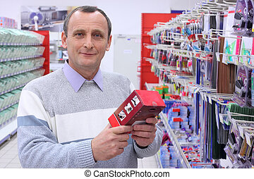elderly man in shop with box in hands