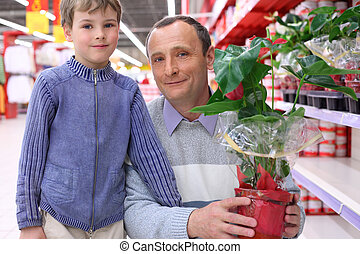 elderly man with boy in shop with  plant in pot