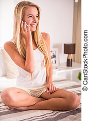 Woman at home - Attractive young woman talking by phone...