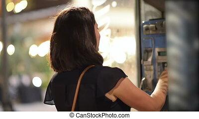 Woman Talking at Public Telephone