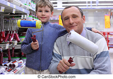 elderly man with  boy in shop with painting rollers in hands