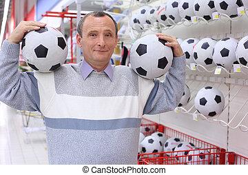 elderly man in shop with footballs in hands