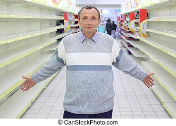 elderly man stands between empty shelves in shop with...
