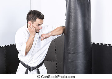 Young man in kimono throwing punches at a heavy punching bag