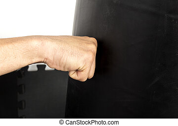 Young man fist punching a heavy bag - Closeup of young man...