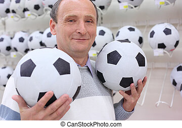 elderly man in shop with footballs in hands