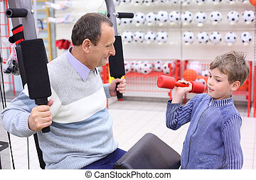 elderly man in shop on sports exerciser and boy with barbell...