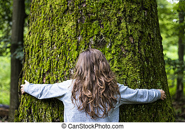 Young girl hugging a big tree in the forest - Portrait of...