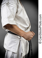 Young man in white kimono and black belt training martial art