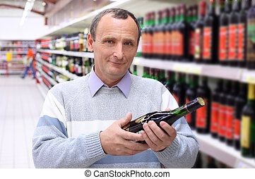 elderly man in shop with wine bottle in hands