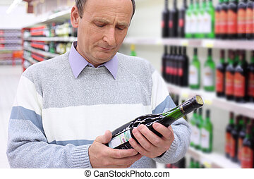 elderly man in shop looks on wine bottle in hands