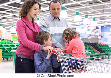 elderly man and young woman with children in shop with empty...