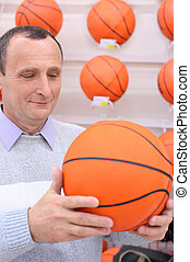 elderly man in shop with basketball ball in hands