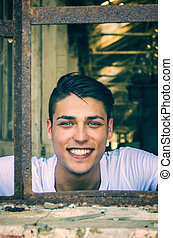Handsome young man with happy expression in rusty window