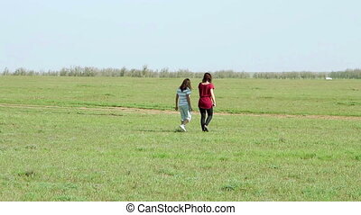 Two woman walking in the meadow at sunny day
