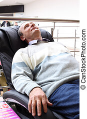 elderly man lies in massage armchair