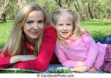 Mother and daughter in park lie on grass in spring