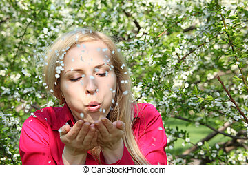 Beauty young woman blowing off petals