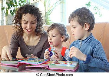 Mother and children play with jigsaw puzzle
