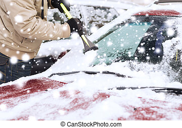 closeup of man cleaning snow from car - transportation,...