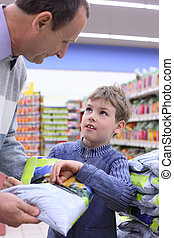 elderly man with boy in shop with package in hands