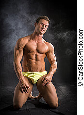 Muscular young bodybuilder in relaxed pose, smiling and...
