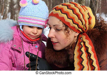 Mother and daughter in wood in winter closeup, mother shows...