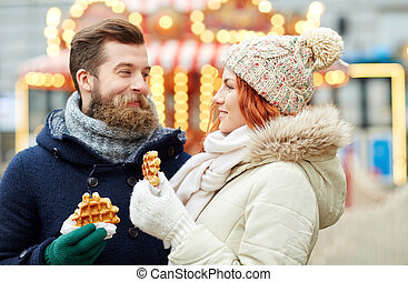 happy couple walking in old town - holidays, winter,...