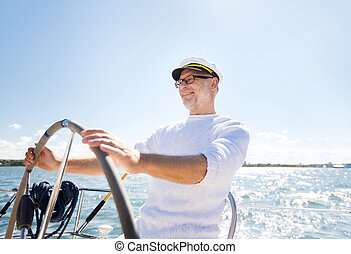 senior man at helm on boat or yacht sailing in sea -...