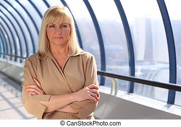 Serious middleaged businesswoman wih crossed hands