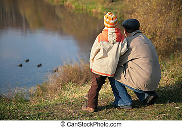 Behind grandfather with grandson in wood in autumn look on ducks in water