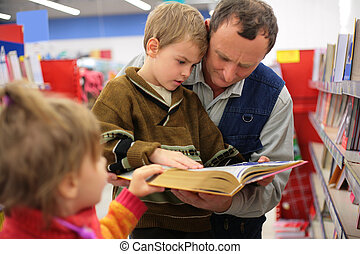 Grandfather and grandson and little girl read the book in a...