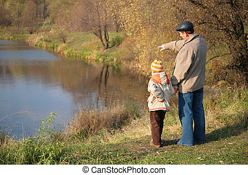 Behind grandfather with grandson in wood in autumn look on water