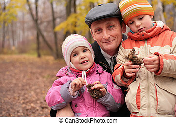 Grandfather with grandchildren in forest in autumn with burr...