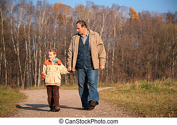 Grandfather and the grandson walk on wood, keeping for hands