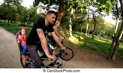 Happy Family Of Three Riding Bicycles In Green Park - SLOW...